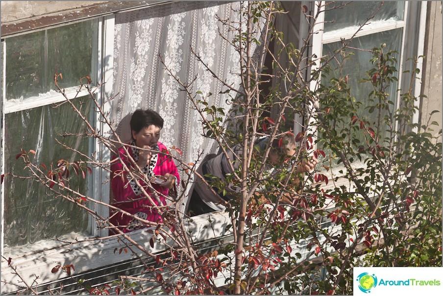 Kiertävät ihmiset aamulla juomaan kahvia ikkunan vieressä.