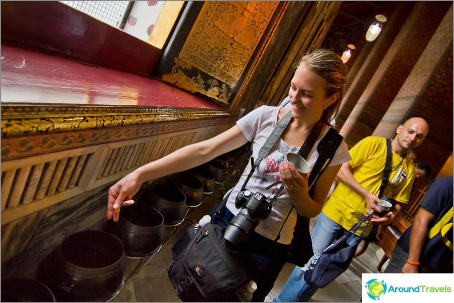 Heitä kolikoita onnellisuudesta Buddhan temppeliin