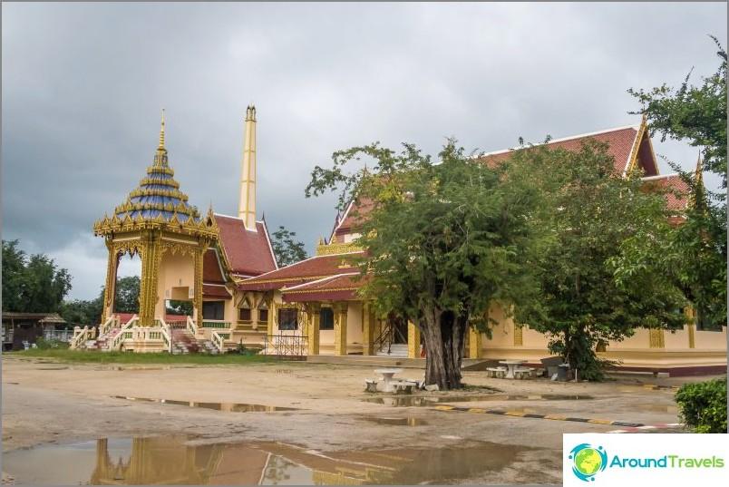 Hyvin thaimaalainen valokuva: krematoriumi, temppeli, puun alla oleva pöytä, lätäkotelot ja maastotien nopea kohouma.
