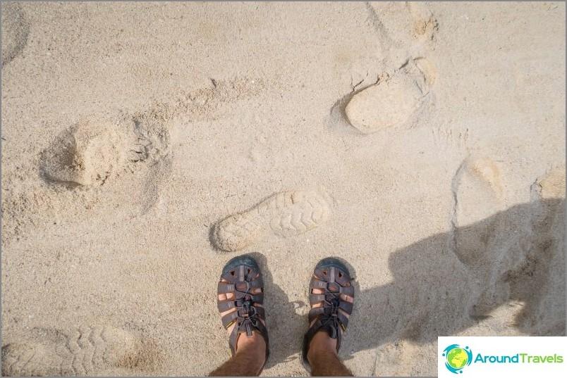 Lähempänä rantaa oleva hiekka on enemmän tai vähemmän normaalia. Vedessä - harjanne kiviä ja kuoria.