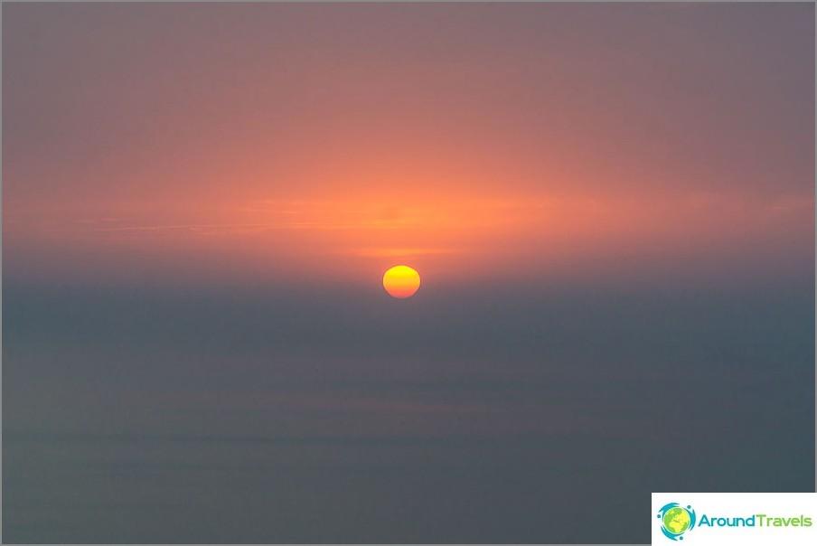Auringonlasku ja pilvet hämärtävät horisonttia