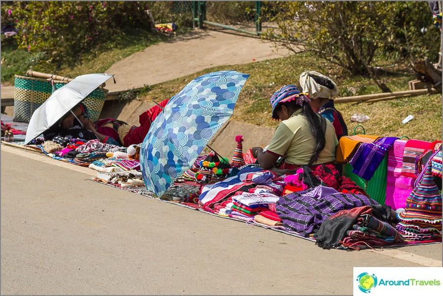 Burmalaiset istuvat peräkkäin sateenvarjojen kanssa ja myyvät jotain