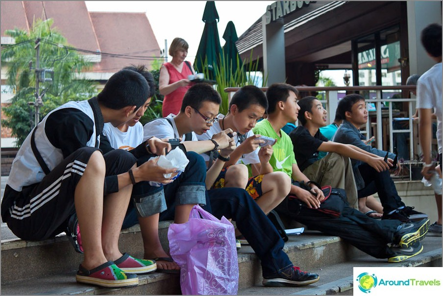 Тайландски ученици, втренчени в телефоните