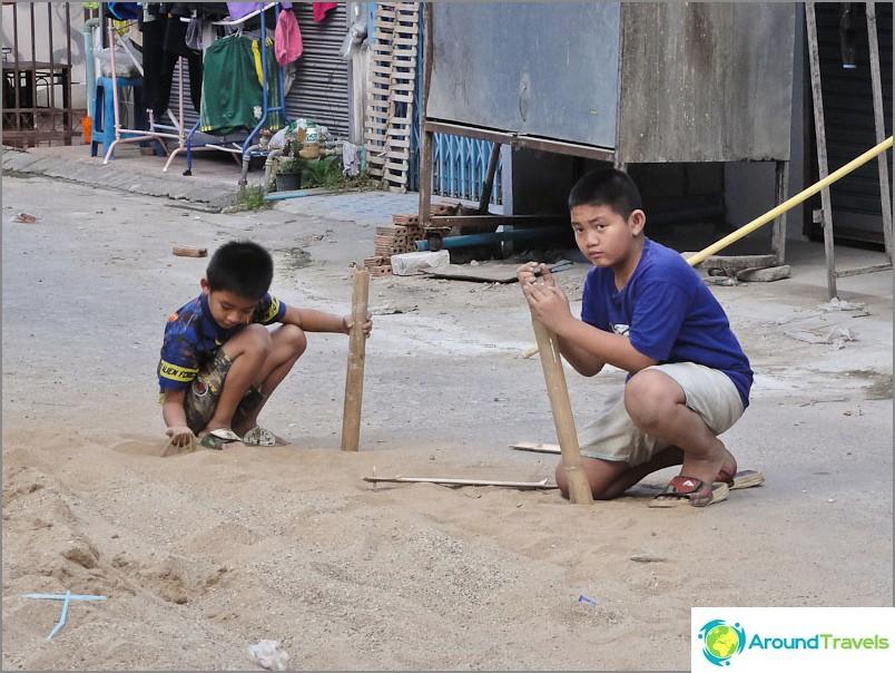 Децата играят с пясък и бамбук.